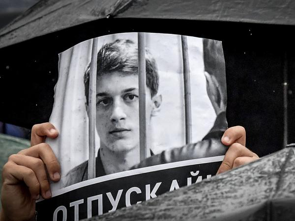 "A protester holds a poster reading ""Free Yegor Zhukov!"" during an August rally in Moscow, after mass police detentions. He was arrested in Moscow on Aug. 1."