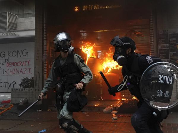 Riot police arrive after protesters vandalized property in Hong Kong on Sunday. Riot police fired tear gas Sunday after a large crowd of protesters at a Hong Kong shopping district ignored warnings to disperse in a second straight day of clashes, sparking fears of more violence ahead of China's National Day.