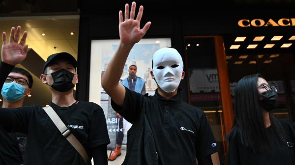 People wear masks and chant slogans outside a shopping mall as they take part in a rally in the Tsim Sha Tsui district in Hong Kong on Saturday.