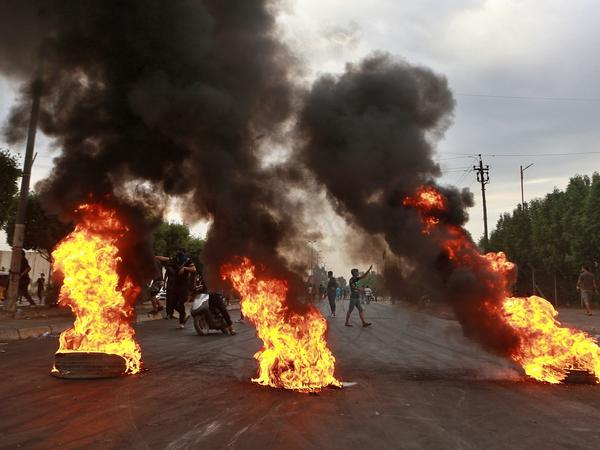 Anti-government protesters set fires and close a street during a demonstration in Baghdad on Sunday after nearly a week of unrest throughout Iraq.