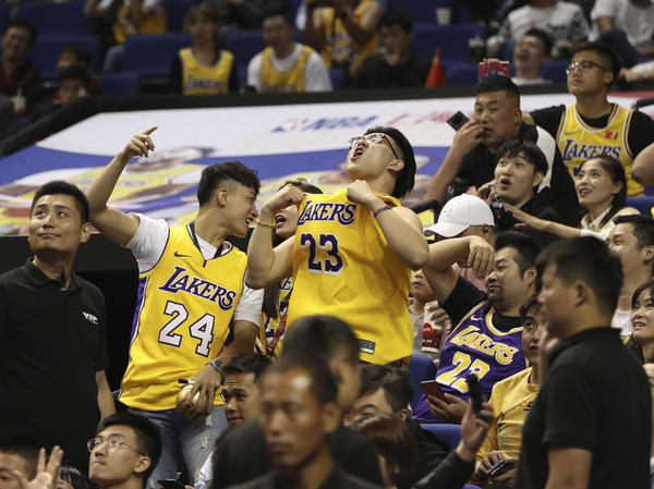 Chinese fans react during a preseason NBA game between the Brooklyn Nets and Los Angeles Lakers in Shanghai on Thursday. While no formal conferences will take place, a league source said the teams can hold their media gatherings independent of the NBA.