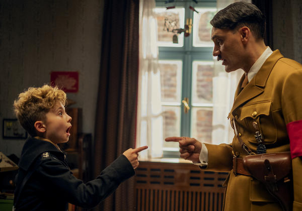 <em>JoJo Rabbit</em> follows a young German boy (Roman Griffin Davis, left) growing up in the Third Reich with his imaginary friend, Adolf Hitler (Taika Waititi, right).