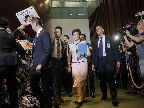 Hong Kong Chief Executive Carrie Lam, center, arrives amid protests as she prepares to deliver her policies at the chamber of the Legislative Council in Hong Kong, on Wednesday.
