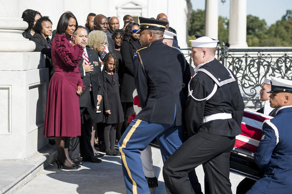 Maya Rockeymoore Cummings (left), Rep. Elijah Cummings' widow, is joined by family members as the late congressman's flag-draped casket is escorted up the east front steps of the U.S. Capitol by a military honor guard.