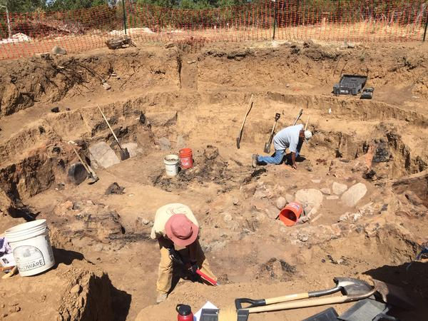 Archaeologists excavating one of the Ancestral Puebloan pit houses in the path of the new highway