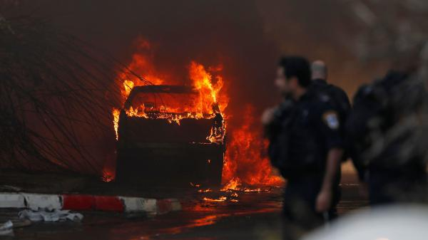 A vehicle burns outside a factory that was apparently hit with rocket fire Tuesday in the southern Israeli town of Sderot. Israel's military announced it had killed a commander of the Palestinian militant group Islamic Jihad in an early morning strike on his home in the Gaza Strip, prompting retaliatory barrages from Gaza.