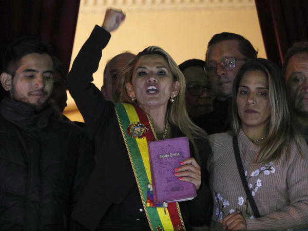 Jeanine Áñez, dressed in a presidential sash, addresses a crowd outside the president's residence in La Paz, Bolivia. The opposition politician declared herself interim president of the country Tuesday.