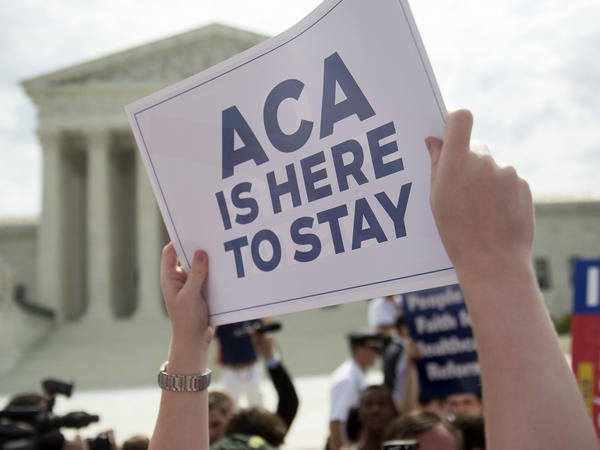 A demonstrator celebrated outside the U.S. Supreme Court in 2015 after the court voted to uphold key tax subsidies that are part of the Affordable Care Act. But federal taxes and other measures designed to pay for the health care the ACA provides have not fared as well.