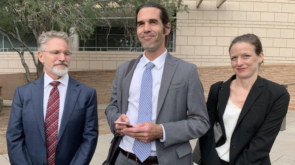 Scott Warren (center) of Ajo, Ariz., celebrates with his attorneys Amy Knight and Greg Kuykendall outside court in Tucson, Ariz., on Wednesday.