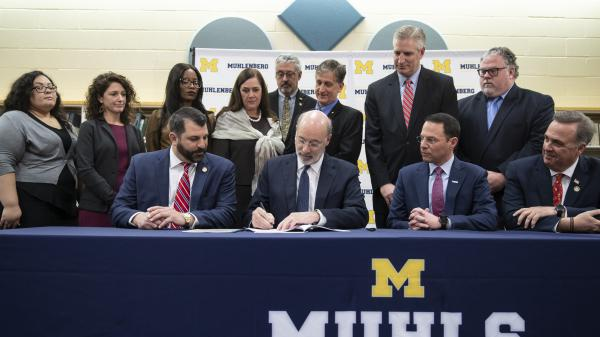 Pennsylvania Gov. Tom Wolf, center, signs legislation overhauling the state's child sex abuse laws.