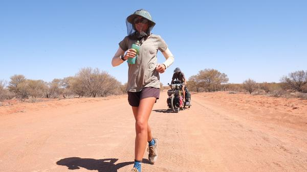 Katie Visco makes her way through the deserts of central Australia, accompanied by her husband, Henley Phillips, on his bike behind her.