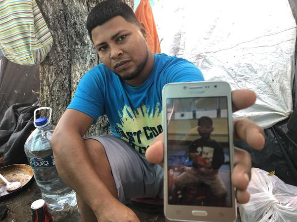 Migrant parents in the tent camps in Matamoros, Mexico, are sending their kids across the border and taking advantage of the rule that unaccompanied children can't be returned to Mexico. Here,  Alexis Martinez holds a cellphone photo of his 7-year-old son Osiel.