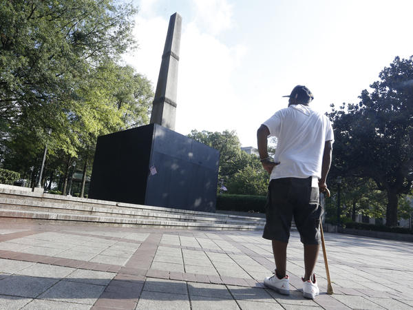A man looks at a Confederate monument in Linn Park this summer in Birmingham, Alabama. Alabama's attorney general sued the city of Birmingham in 2017 for covering the inscriptions at the base of the monument.