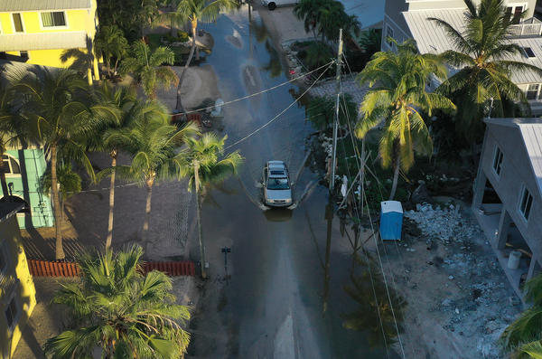An aerial view from a drone shows a car as it drives through a street flooded with ocean water in Key Largo, Fla., on Oct. 22.