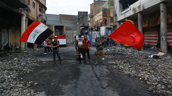 Anti-government protesters wave flags on Rasheed Street in Baghdad on Sunday.