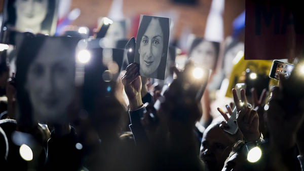 Demonstrators raise pictures of slain journalist Daphne Caruana Galizia during a demonstration outside Maltese Prime Minister Joseph Muscat's office late last month. During a televised address Sunday night, the premier announced he would be resigning amid pressure over the reporter's death.