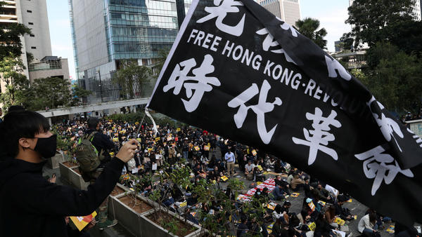 """""""China urges the U.S. to correct its mistake and stop meddling in Hong Kong affairs,"""" a government spokesperson says, as China retaliates for U.S. support of pro-democracy demonstrators. Here, an activist holds a flag at a lunchtime protest Monday at Chater Garden in Hong Kong."""