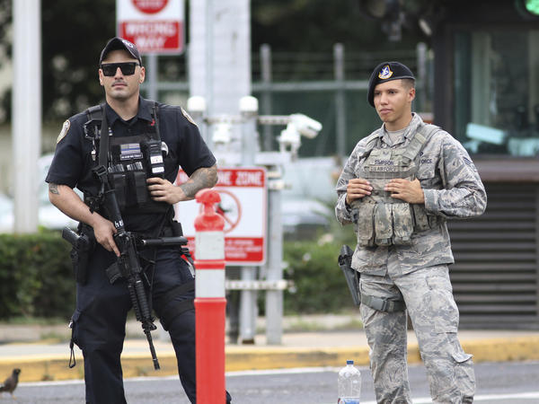 Security guards outside the main gate at Hawaii's Joint Base Pearl Harbor-Hickam following the shooting. The Navy says the gunman was assigned to a nuclear-powered attack submarine currently in port.