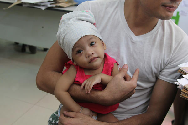 A father in the Philippines holds his child, who was immunized for measles.