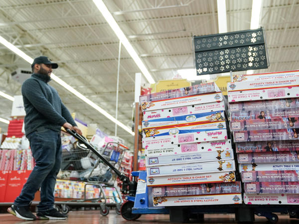 An employee stocks the toy section of a Walmart on Black Friday in King of Prussia, Pa.