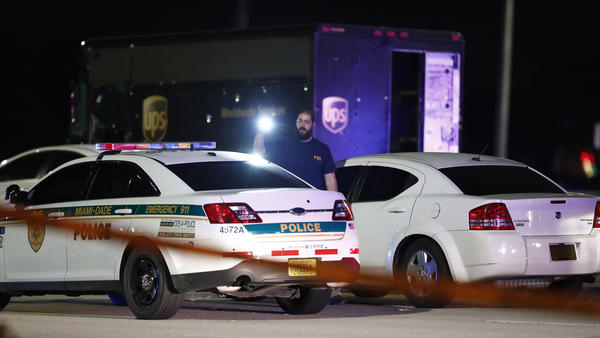 An FBI official at the scene of a shooting, Thursday in Miramar, Fla. Four people, including a UPS driver, were killed in the shootout between the armed robbers and police authorities.
