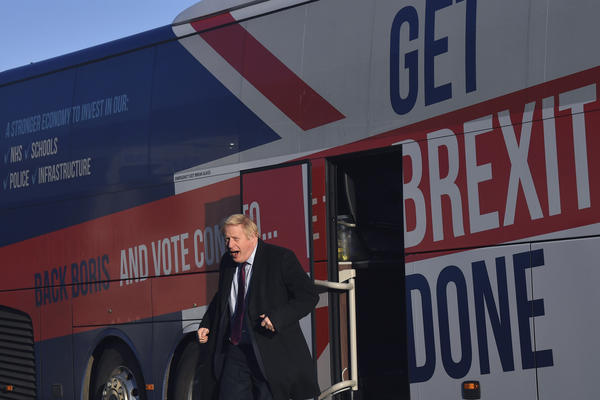 "Britain's Prime Minister Boris Johnson gets off his election campaign bus — emblazoned with the slogan ""Get Brexit Done"" — to visit Washington, England, on Monday. Britain goes to the polls on Thursday."