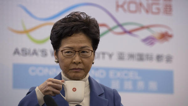 Hong Kong Chief Executive Carrie Lam sips from a mug during her news conference Monday in Beijing, after meeting with Chinese officials over the continued unrest roiling her semiautonomous region.