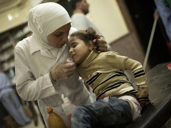In a photo from October 2012, a nurse treats a girl wounded by Syrian Army artillery shelling at Dar El Shifa hospital in Aleppo, Syria.
