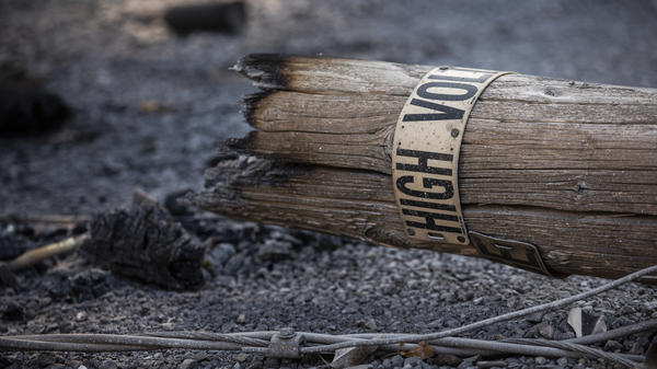 A fallen PG&E utility pole lays on a property burned during a wildfire. The company has several settlement deals meant to clear liabilities stemming from fires sparked by its equipment.