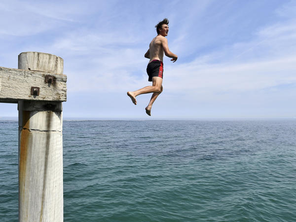 A swimmer jumps from a jetty in an effort to cool off in Adelaide, Australia, as the country experiences record temperatures.