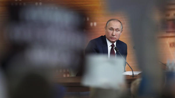 "Russian President Vladimir Putin speaks Thursday during his annual news conference in Moscow. During the four-hour session, the longtime Russian leader called the U.S. impeachment process ""far-fetched,"" making the prediction that Donald Trump will be acquitted in the Senate."