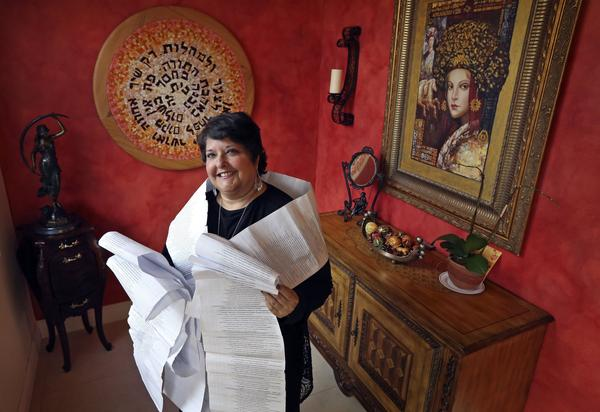 Genie Milgrom, pictured in 2013, stands in the entryway of her Miami home wrapped in a long family tree, filled with the names of 22 generations of grandmothers. Raised Catholic, Milgrom traced her family's hidden Jewish roots with the help of a trove of ancient family recipes written down by the women of her family over generations.