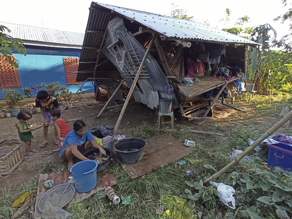 Residents outside their home,  damaged by Typhoon Phanfone at Concepcion town, Iloilo province, central Philippines on Friday.