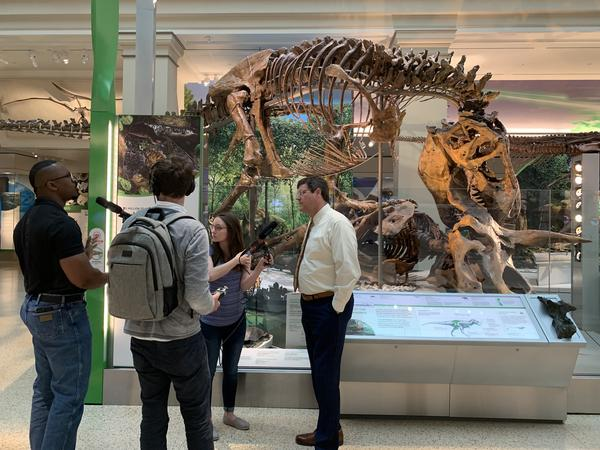 Joshua, engineer Jayk Cherry, producer Amanda Williams and Smithsonian's National Museum of Natural History director Kirk Johnson in front of the T. rex during a tour of the museum's fossil hall.