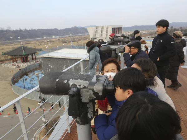 Visitors celebrating the New Year use binoculars to watch North Korean territory Wednesday, near the border between North and South Korea.