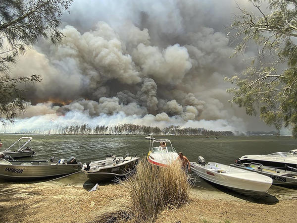 Boats are pulled ashore as smoke and bushfires rage behind Australia's Lake Conjola on Thursday. Thousands of tourists fled the country's fire-ravaged eastern coast this week ahead of worsening conditions.