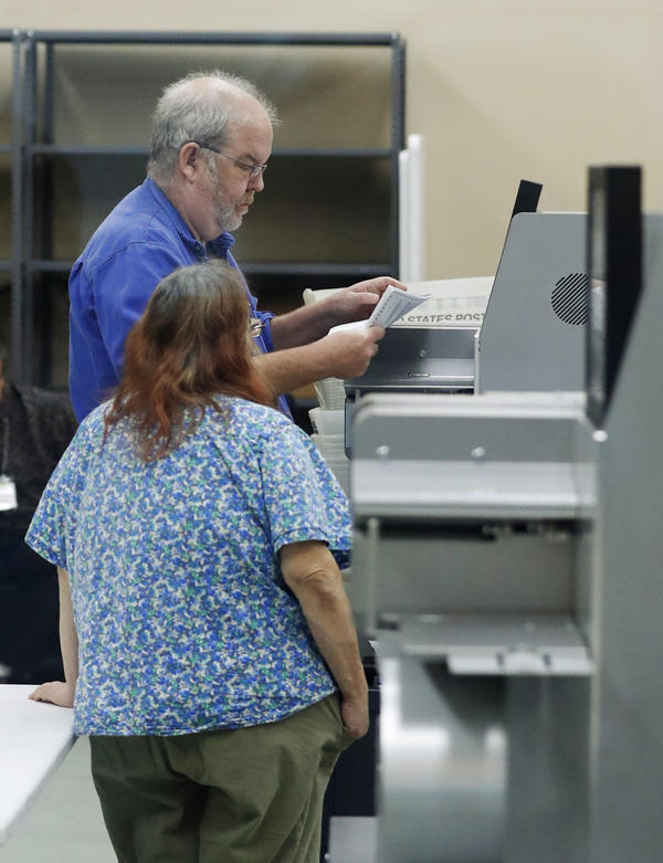 Employees at the Broward County Supervisor of Elections office calibrate machines before counting ballots, Monday, Nov. 12, 2018, in Lauderhill.