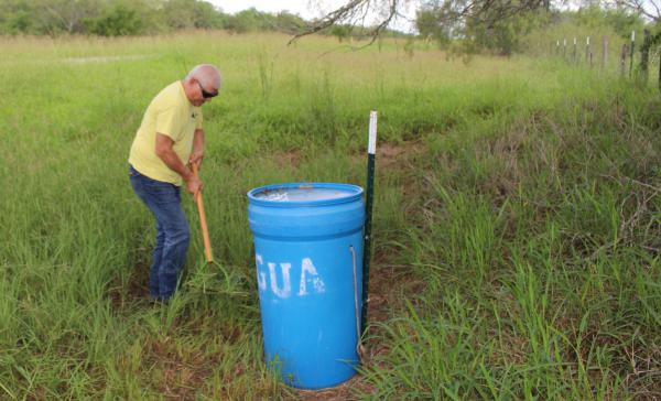 Eddie Canales of the South Texas Human Rights Center builds a water station in Brooks County.