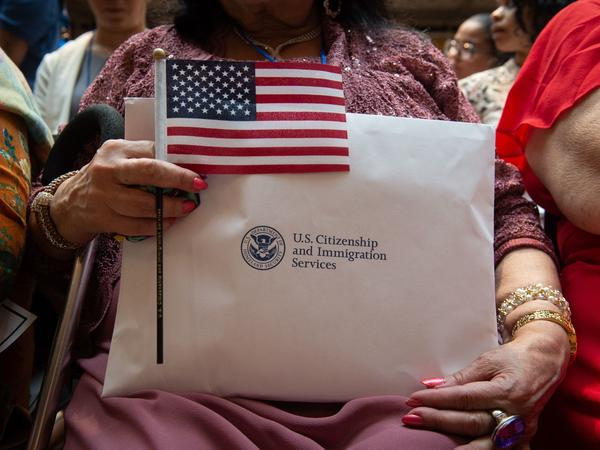 A newly sworn-in U.S. citizen holds the U.S. flag and paperwork during a 2018 naturalization ceremony in New York City. The Department of Homeland Security has agreed to share its records with the U.S. Census Bureau to help produce data about the U.S. citizenship status of every person living in the country, as ordered by President Trump.