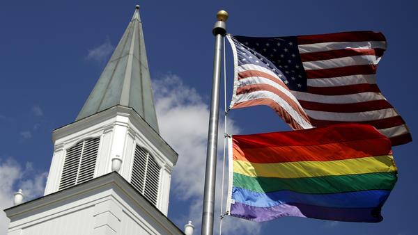 A rainbow gay pride flag flies below the U.S. flag last year in front of the Asbury United Methodist Church in Prairie Village, Kan.