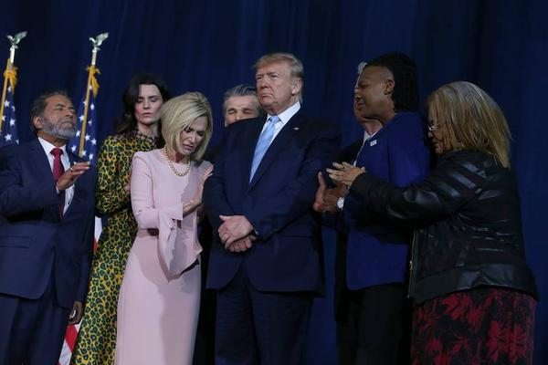 Christian faith leaders pray around President Trump before his speech to Evangelicals on Friday at the King Jesus Ministry megachurch in West Kendall.