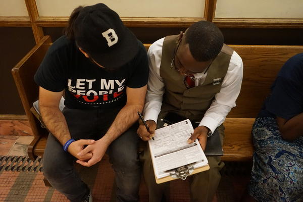 Dolce Bastien, right, registers to vote after getting his rights restored in Miami.