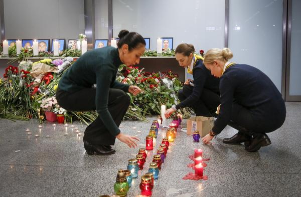 Colleagues of the flight crew members of the Ukrainian 737-800 plane that crashed on the outskirts of Tehran, light candles at a memorial inside Borispil International Airport near Kyiv on Wednesday.
