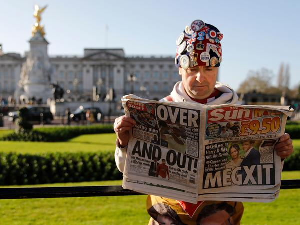 John Loughery, a fan of the royals, reads the day's news outside Buckingham Palace in London on Thursday, following the announcement that Prince Harry and Meghan Markle plan to step down as senior members of the royal family.