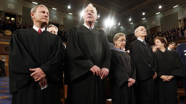 Chief Justice John Roberts (left) stands with his colleagues on the 2014 Supreme Court. Unlike during the Clinton impeachment trial, the membership and the direction of the court has changed in the past few years.