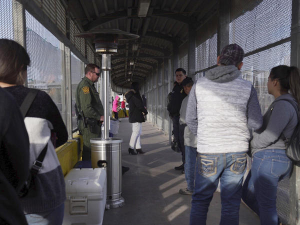 A Border Patrol agent and a U.S. Customs and Border Protection agent oversee the people waiting to cross into the U.S. from Matamoros, Mexico, at the Port of Entry in Brownsville, Tex., Tuesday, last month.