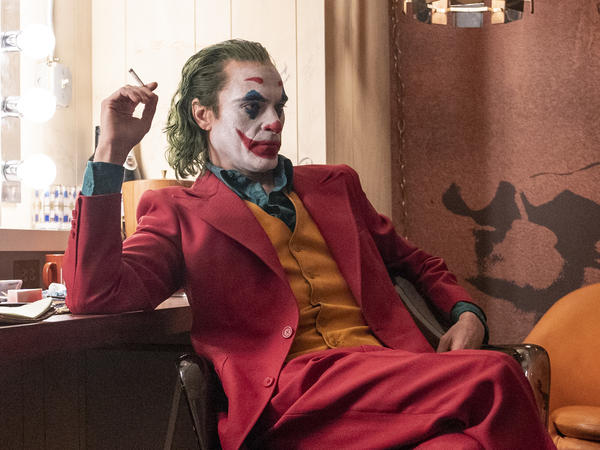 Joaquin Phoenix is Arthur Fleck, a party clown and aspiring stand-up comic who struggles with mental illness and turns violent in <em>Joker</em>.