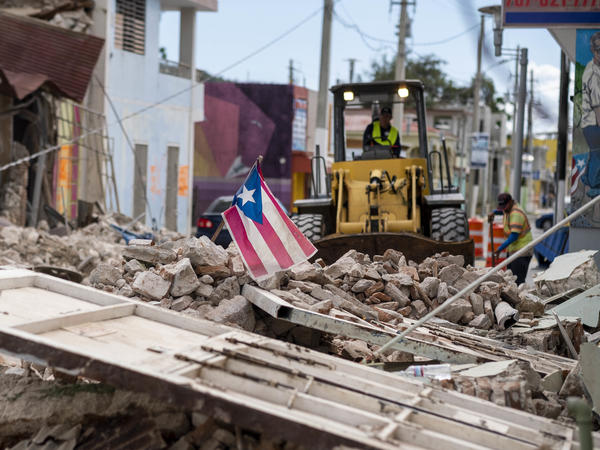 A Puerto Rican flag waves on top of a pile of rubble as debris is removed from a main road in Guánica.