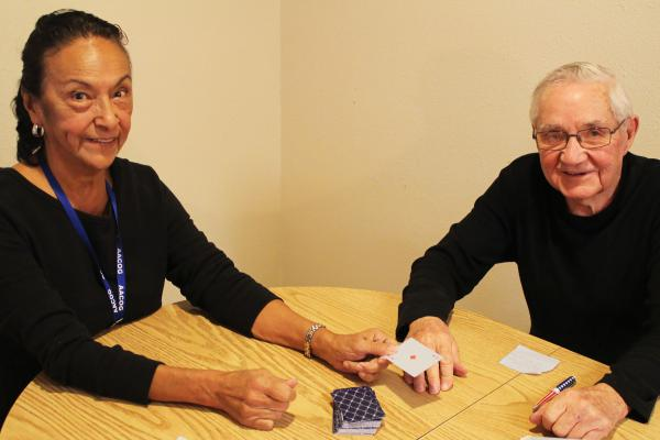 World War II veteran Gerry Bennett, 92, plays cards with Gloria Estrello, a volunteer with the Choose Home Senior Corps program.