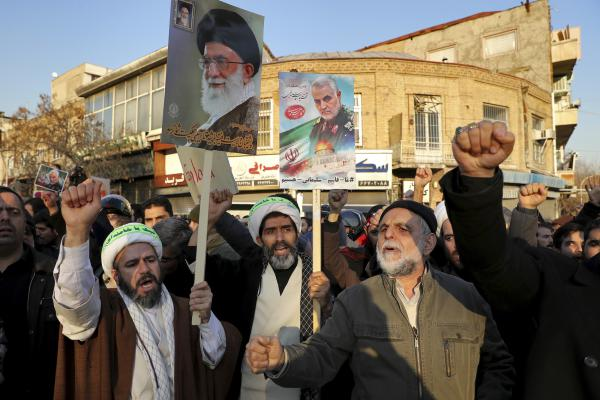 Hardline protesters chant slogans while holding up a poster of Gen. Qassem Soleimani and Supreme Leader Ayatollah Ali Khamenei, during a demonstration in front of the British Embassy in Tehran, Iran, Sunday, Jan. 12, 2020. (Ebrahim Noroozi/AP)